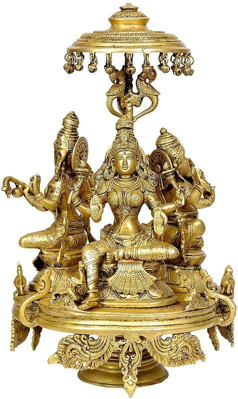 The Great Trinity of Ganesha, Lakshmi and Saraswati Seated on Moving Chowki with Parasol